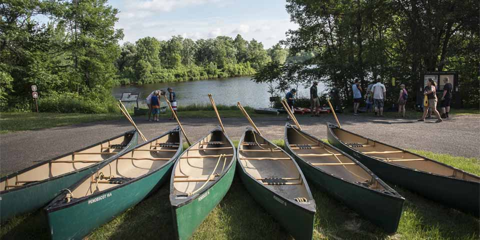 Canoes are lined up near a river as a group prepares to launch.