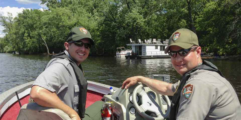 Two park rangers smile from a boat.