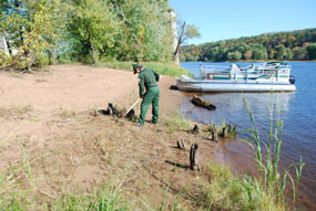 A uniformed park ranger rakes the sand.  A pontoon boat is tied up to the shore. A tree line is in the background.