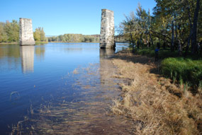 Two stone pillars stand in the water; they were once part of a railroad bridge that crossed the river here between two islands.