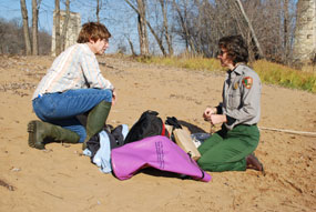 A man in jeans and a shirt and a woman in the gray and green national park service field uniform kneel and talk on a sandy shore.