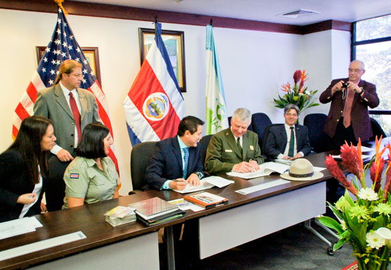 U.S. and Costa Rican flags are displayed behind desks at which two men sign documents, while others look on.