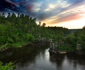 Green tree topped rocky gorge with river at sunrise