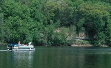 pontoon travelling in front of cliff with rocks and trees
