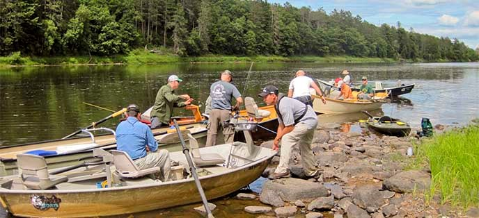 People in boats prepare to get on a river.