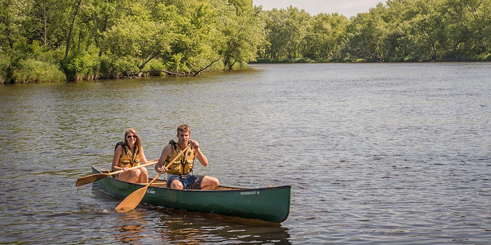 Two canoers paddle on a river through a forested landscape.