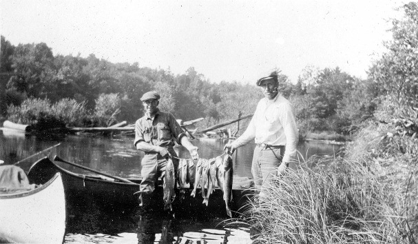 A historic photo of two friends displaying the days catch from the St. Croix. (Photo courtesy the Riegel Collection)