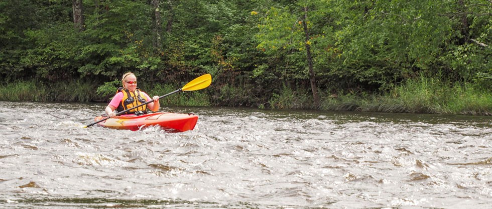 A woman paddles a kayak in moving water.