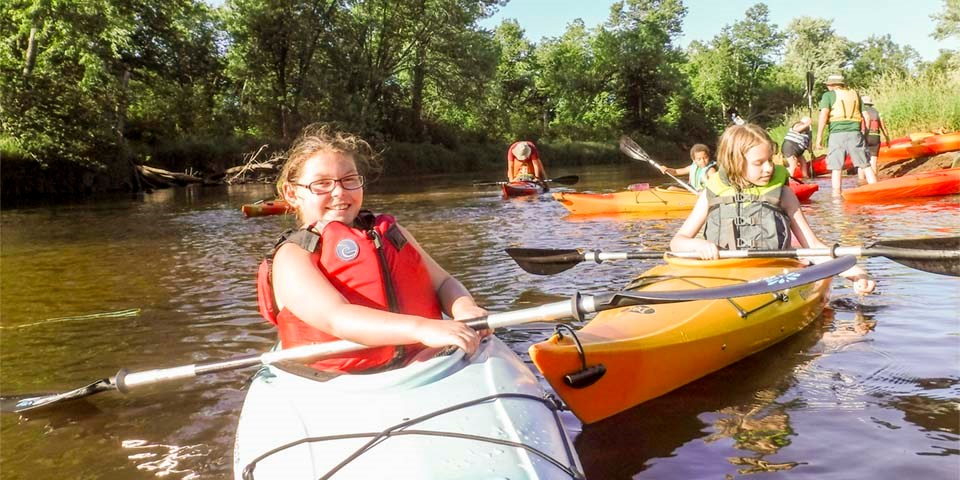 Young paddlers in kayaks start a trip on a river.
