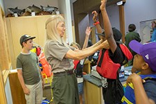 A ranger checks the lifejacket of a young visitor indoors.