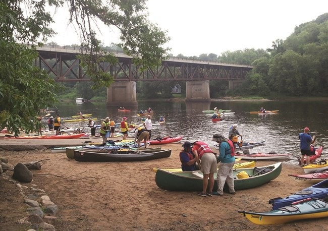 Large group of canoers and kayakers crowd a beach along river