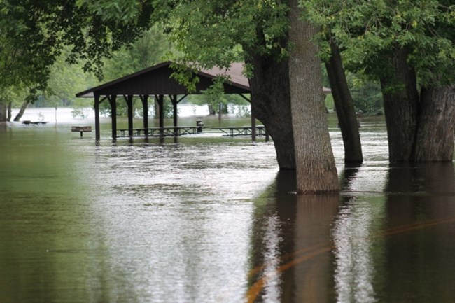 The St. Croix River flows over the road and through a picnic shelter at Osceola Landing on Saturday, June 23, 2012. NPS photo.