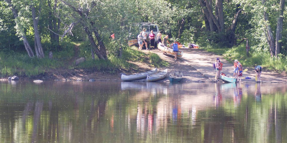 A group of people unload canoes at a river landing.