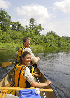 Two people in a canoe turn to smile