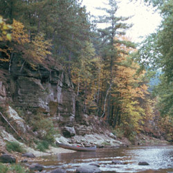 Wooded cliffs by a river in fall.