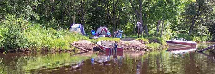 Tents are set up next to a river with boats along the shoreline.