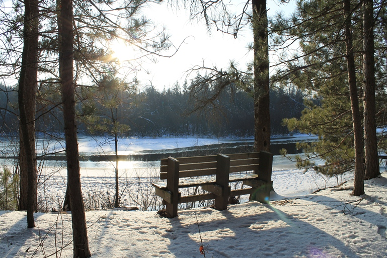A bench overlooks the partially frozen waters of the Namekagon River in this image. NPS photo.
