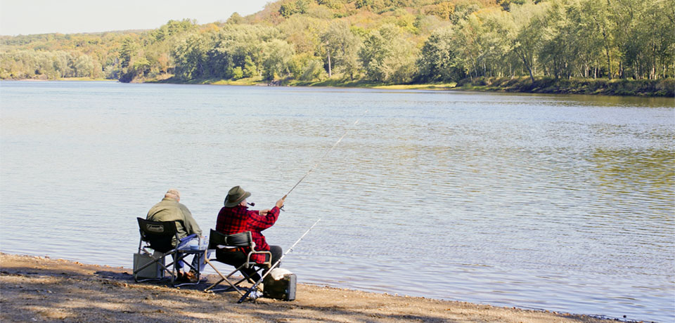 Two men sit in chairs fishing at a river.