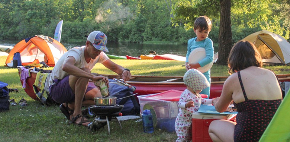 A family cooks near a tent next to a river.
