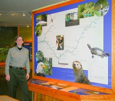 A ranger stands next to a map display.