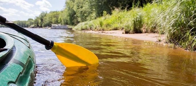 A yellow paddle dips into a river from the side of a kayak.