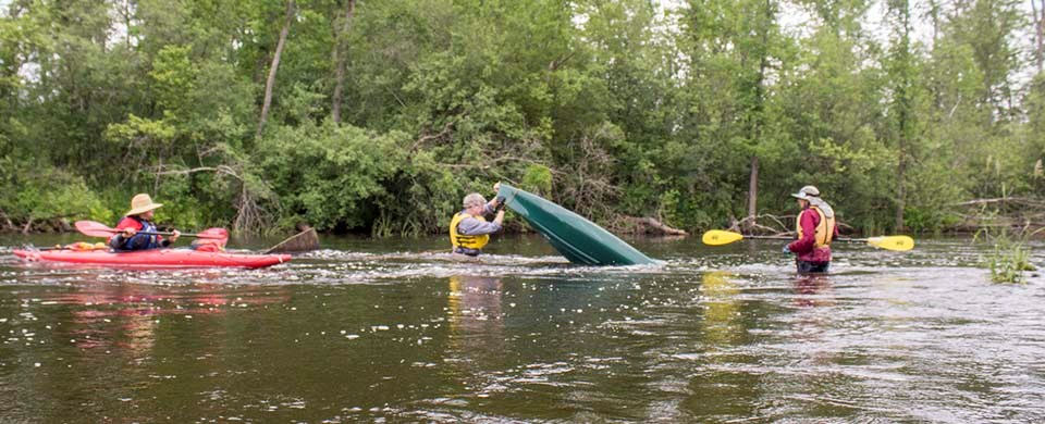 A paddler turns a flipped kayak over in a river while others watch.