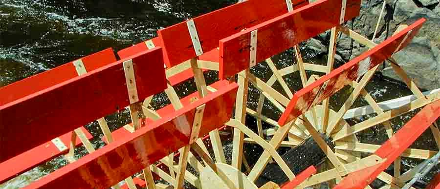 A red paddlewheel turns in water.