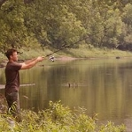 A man casting with a fishing rod towards water