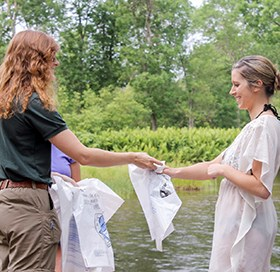 A volunteer hands out litter bags to visitors.