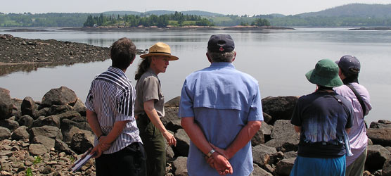 Park employee talks with four visitors with a view of the island in the background.
