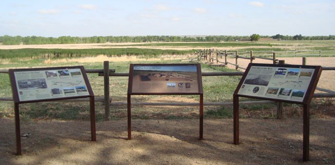 three wayside exhibit panels in front of a view of wood rail fences crossing an open prairie