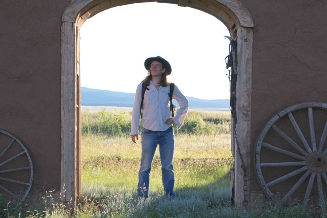 Student Conservation Association intern Noah stands in a doorway of a historic site surrounded by prairie.
