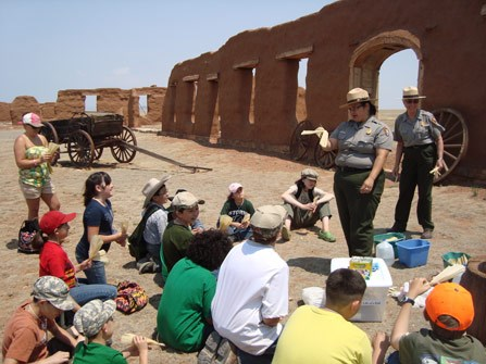 Two rangers stand in front of a group of kids seated on the ground facing a historic site.