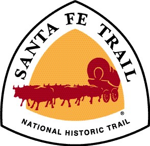 "Rounded triangular graphic with red covered wagon pulled by six oxen against a yellow background, surrounded by white band containing the text, ""Santa Fe Trail National Historic Trail"""