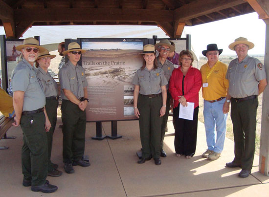 six park rangers and two others are standing on either side of an exhibit kiosk and facing you