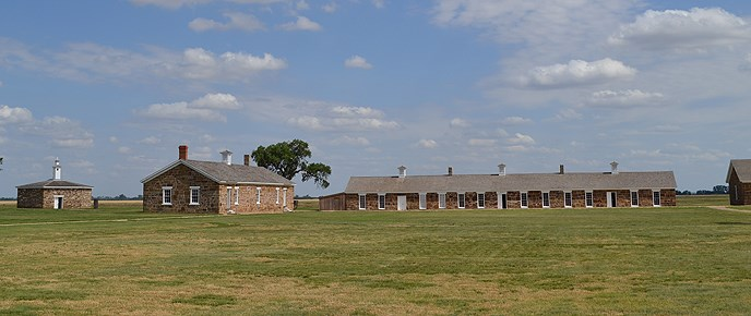 grass in the foreground, brick building farther back, blue sky