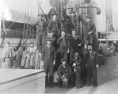 Sailors standing on the deck of a sailing ship.