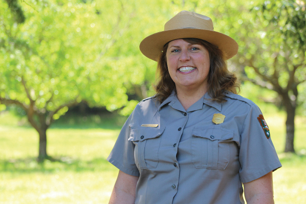 Chief of Cultural Resources Gretchen Stromberg wearing a NPS uniform, standing outside with trees in the background