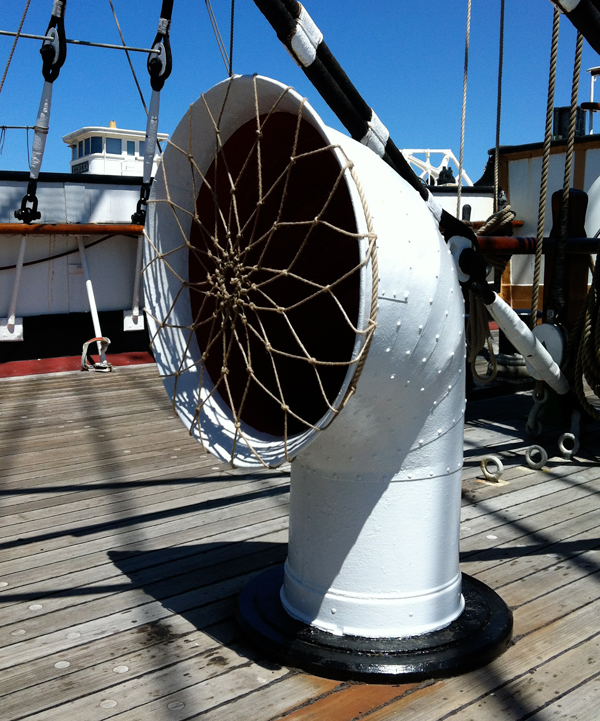 A white-colored ventilator with a large opening on the deck of a ship.