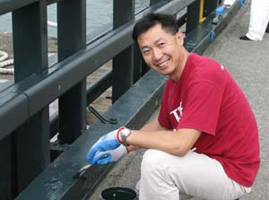 A man in a red t-shirt using a paintbrush on railings along a pier.
