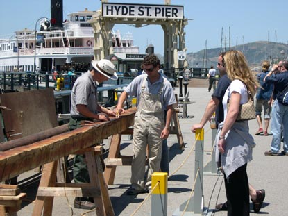 People on Hyde Street Pier working on a spar (mast) for a boat.