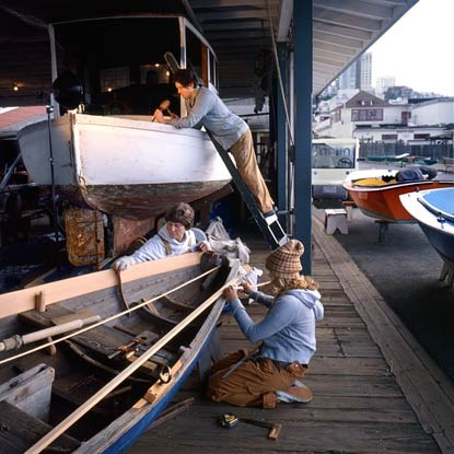 Park volunteers working on two small wooden boats on Hyde Street Pier.