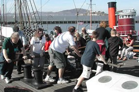 Visitors turning the capstan on the sailing ship Balclutha. A capstan is a type of winch used on ships to lift heavy objects such as the anchor.