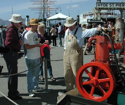 Park volunteer on Hyde Street Pier standing next to a red Hick's engine and talking to interested park visitors.