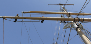 Three park rangers aloft on BALCLUTHA standing on the footrope and holding onto the mainmast yard.