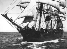 A black and white photo of a full rigged vessel under sail.