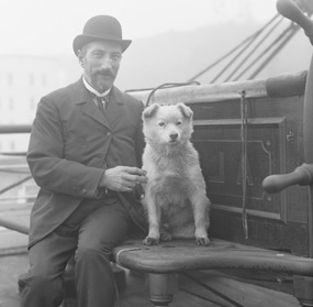 A man in a bowler hat seated next to a white dog near the helm of a sailing ship.