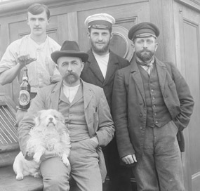 Four men and a white dog posing on the deck of a 19th century sailing vessel.