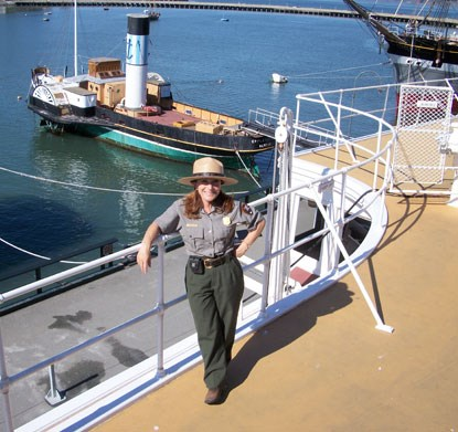 Teacher and Park Ranger Cynthia Harb standing on the deck of a ship at Hyde Street Pier.