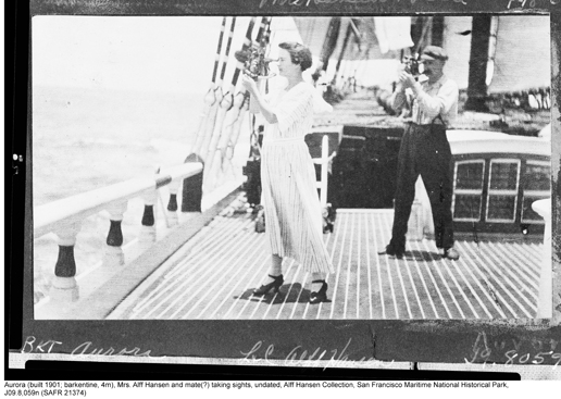 A historic photo of a woman on the deck of a sailing ship using a sextant.